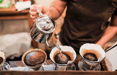 main qui versent eau dans une cafetière