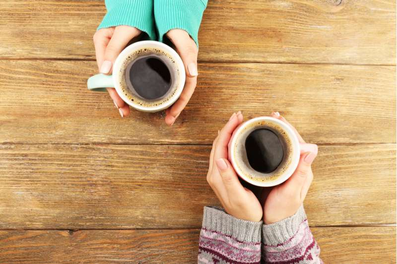 deux mains de femme qui tiennent du café